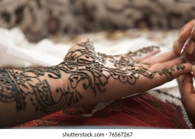Henna being applied to hand of an Indian bride