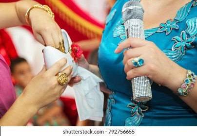 Henna extracts from the container. They put their hands henna of the bride . Drawing henna at the Henna party. They put money in their hands