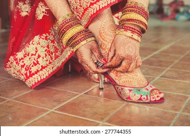 Henna mehndi wedding design on the feet and hands of red dressed up bride