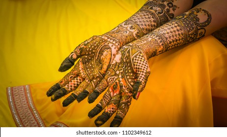 Henna painting, mehendi on bride's hands with the yellow dress background. Wedding preparation in India.