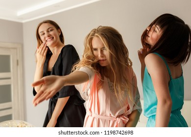 Hen-party concept. Three charming, beautiful young girls dancing, spending time with pleasure, while celebrating the bridal shower in pajamas, at home. Women party.
