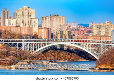 Henry Hudson Bridge spans Spuyten Duyvel Creek, in New York City. Harlem apartment buildings shine under the late afternoon light.