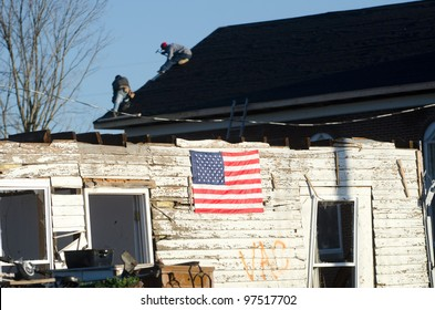 HENRYVILLE, IN, USA - MARCH 10, 2012 - Workers fix the roof of a church while an American flag hangs on a home damaged during an EF4 tornado that struck Henryville, Indiana, USA, on March 2, 2012. Henryville, March 10, 2012