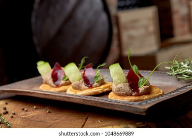 Hepatic pate from a duck on bread toast cucumber, jelly and a stalk of peas