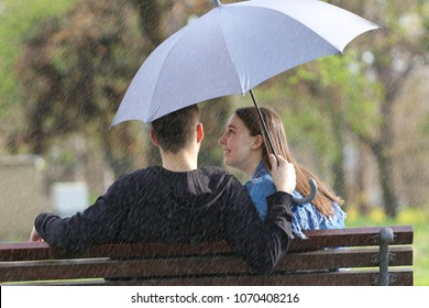 Heppy young Couple sitting on bench on the rainy spring day with umbrella