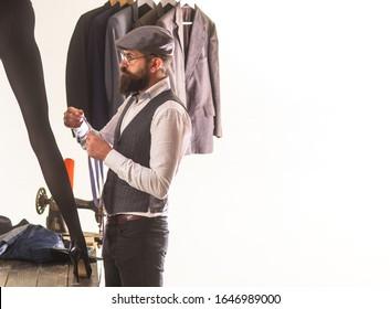 Her dressmaker is an artist. Professional dressmaker or fashion designer at work. Bearded man dressmaking female clothes in dressmaker salon. Fashionable dressmaker making clothing, copy space.