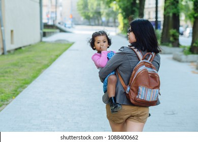 with her ecuadorian mother carry away her dark skinned toddler baby girl on city street. Back view. No to violence against children concept.