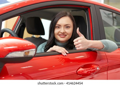 Her first car. Portrait of a beautiful cheerful brunette female smiling to the camera showing thumbs up posing sitting in a red car at the car salon