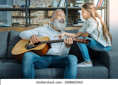 Her first serenade. Beautiful young lady smiling while sitting on a sofa and listening to her talented granddad singing and playing guitar.