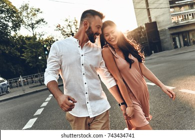 Her happiness is everything to him. Beautiful young couple holding hands and smiling while walking through the city street