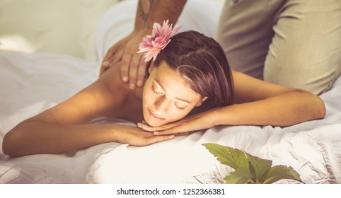 For her only the best. Young men and women at nature. Men gives women a massage treatment.