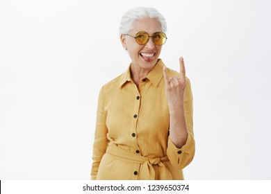 Her sould is young. Portrait of joyful pleased and carefree enthusiastic grandmother with grey hair in stylish sunglasses and yellow coat sticking out tongue showing rock n roll gesture