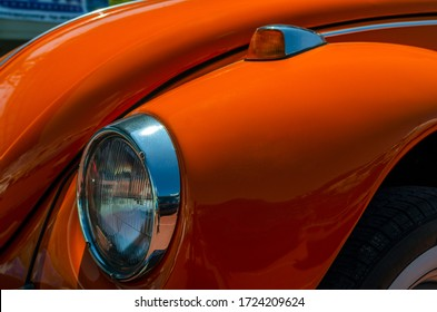 Heraklion, Crete / Greece - Jul 6, 2013: Close up detailed view of the front fender with the headlight and the turn signal light of an orange classic Volkswagen Beetle. Illustrative editorial, concept