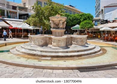 HERAKLION, CRETE, GREECE - JULY 24, 2011: Tourists rest near Venetian Morosini fountain in Lions Square at the city centre