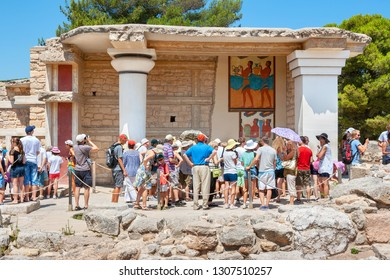 HERAKLION, CRETE, GREECE - JULY 27, 2011: Tourist group on a guided tour in Knossos palace near south Propylaeum with procession fresco