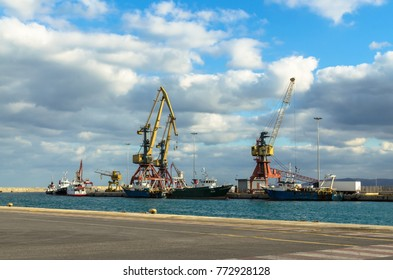 Heraklion, Crete, Greece - November, 2017: In the foreground - sea and pier of the  port of Heraklion, loading equipment, ships, boats,  cars,  in the background - mountains