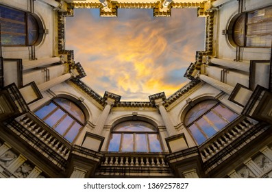 Heraklion, Crete Island / Greece - March 27, 2019: Venetian Loggia, looking up to the atrium from the building's courtyard. Loggia houses the town hall of Heraklion. Colorful sunset with cloudy sky