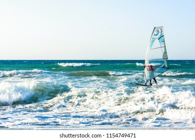 Heraklion, Greece - 07.11,2018:Windsurfers in the sea on Crete on sunset. Windsurfing in Heraklion. Greece