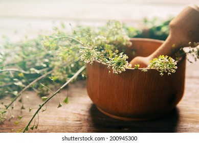 Herb capsella in mortar with pestle on wooden background, side view, medicinal herb