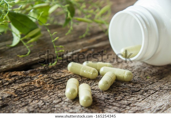 Herb capsule with green herbal leaf and bottle