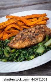 herb chicken breast meal with greens and sweet potato fries on rustic table