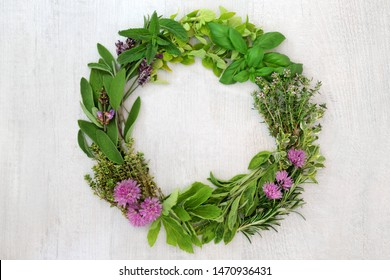 Herb leaf and flower wreath with a selection of fresh herbs with flowers on rustic wood background with copy space.