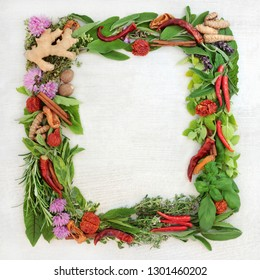 Herb leaf and spice wreath with a selection of fresh herbs with flowers on rustic wood background with copy space.