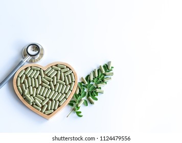 Herb  medicine  in  capsule  from  various  herbs  on  wood  shape  of  heart  and   stethoscope  for  healthy  life  style
