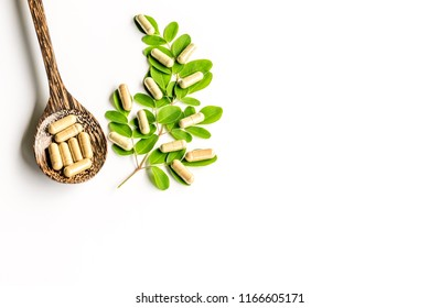 Herb  medicine   capsules   from  moringa leaves   on  wooden  spoon   with  white background.