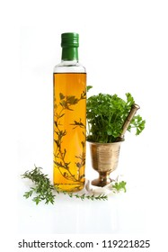 Herb oil and a brass mortar on white background