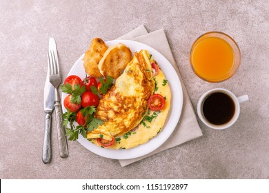 Herb omelette with chives, cherry tomatoes and parsley with panini toasts. Coffee and orange juice. Breakfast