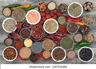 Herb and spice food selection dried and fresh on rustic wood background. With dried ring of fire, padron and scorpio chilli peppers. Top view.