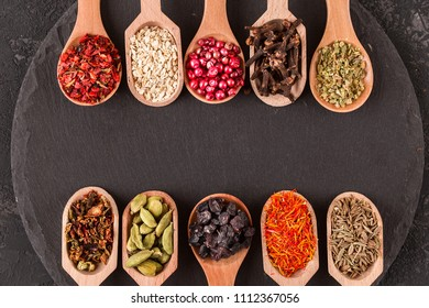 Herb and spice ingredients on slate over dark concrete. Background of various kinds of dry spices. Organic food, healthy lifestyle, space for text