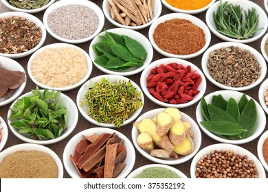 Herb, spice and super food selection for mens health in porcelain bowls over hessian background. Used in natural alternative herbal medicine. Selective focus.