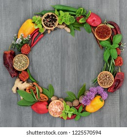 Herb and spice wreath with a selection of dried and fresh herbs and flowers on rustic wood background.