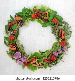 Herb and spice wreath with a selection of dried and fresh herbs and  flowers on rustic wood background with copy space.