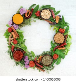 Herb and spice wreath with a selection of dried and fresh herbs and  flowers on rustic white wood background with copy space.