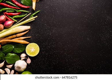 Herb and spicy ingredients for making Thai food or tomyam. Recipe book with fresh herbs south asia and spices on wooden black background, (concept thai food),top view
