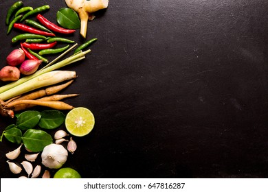 Herb and spicy ingredients for making Thai food or tomyam. Recipe book with fresh herbs south asia and spices on black background, (concept thai food),top view