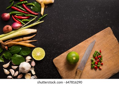 Herb and spicy ingredients and tools for making Thai food or tomyam. Recipe book with fresh herbs south asia and spices on wooden black background, (concept thai food),top view