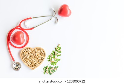 Herbal  alternative  medicine  capsules  in  wooden  plate,red  heart  and  stethoscope   on  white  background