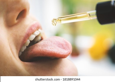 herbal alternative medicine and dietary supplements - woman taking cbd hemp oil drops in mouth from dropper. medical cannabis