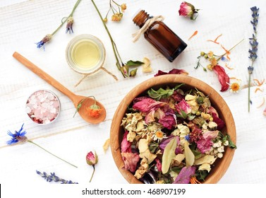 Herbal blend of various dried medicinal flowers, essential oil, bottle, sea salt. Natural skincare. Top view, focus on wooden bowl with colorful plants.