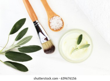 Herbal botanical facial mask with holistic plant salvia. Ingredients for home spa top view: Jar of face lotion, green plant leaves, sea salt, white wooden table background