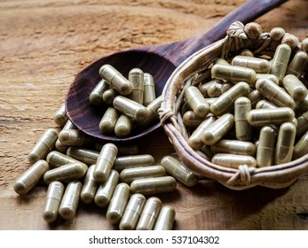 Herbal capsule pill with wooden spoon, grunge wooden table background