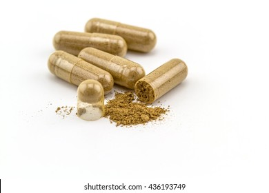 Herbal capsule and powder on white background.