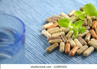 herbal capsules with mint leaves and glass of water