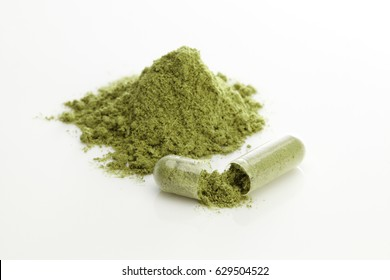 Herbal capsules and powder on white