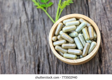 Herbal capsules powder in wooden bowl, top view, healthy eating with herb for happy living life