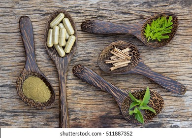 Herbal capsules from various herbs on wooden spoon for healthy lifestyle